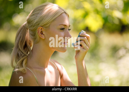 A young blond woman sitting in the grass using a asthma inhaler - Stock Photo
