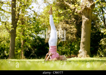 A young woman doing a shoulder stand outside - Stock Photo
