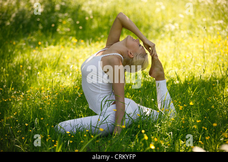 A young woman practicing yoga outside, pigeon pose - Stock Photo