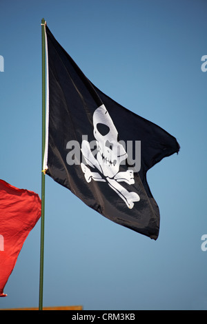 Jolly Roger pirate flag blowing in the wind at Poole - Stock Photo