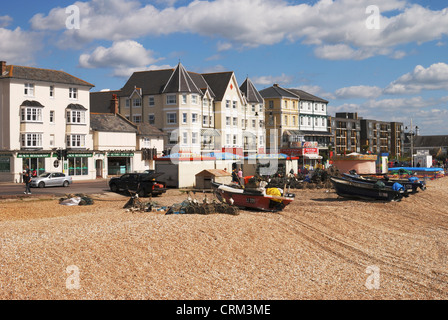 Shingle Beach and seafront at Bognor Regis in West Sussex. England. With fishing boats drawn up out of water. - Stock Photo