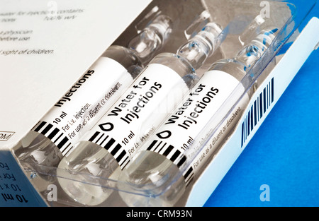 Glass ampoules containing water for injections half removed from their packaging. - Stock Photo