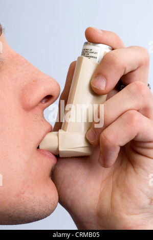young male using his asthma pump - Stock Photo