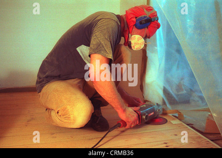 Berlin, a man drags floorboards with a sander - Stock Photo