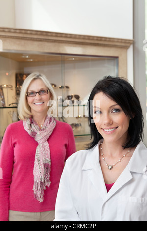Portrait of happy mid adult optician and customer wearing glasses - Stock Photo