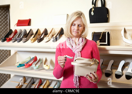 Mature woman looking at price tag of purse in store - Stock Photo
