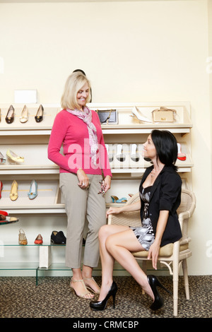 Happy mid adult woman trying on heels while mature female looking in shoe store - Stock Photo