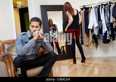 Young man sitting on armchair looking away while girlfriend looking herself in mirror - Stock Photo