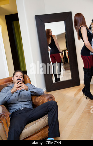 Young man sitting on armchair using mobile phone while girl looking at herself in mirror - Stock Photo