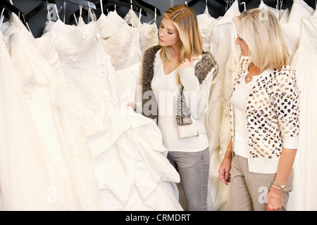 Mother and daughter selecting bridal gown in boutique - Stock Photo