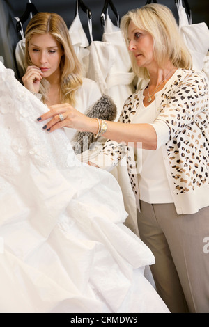 Mother selecting wedding dress for young daughter in bridal store - Stock Photo