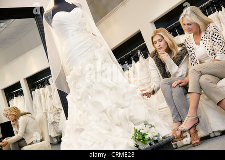 Mother and daughter sitting on sofa while looking at elegant wedding dress in bridal store - Stock Photo