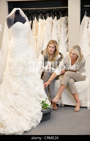Beautiful young woman sitting with mother while looking at wedding gown in bridal store - Stock Photo