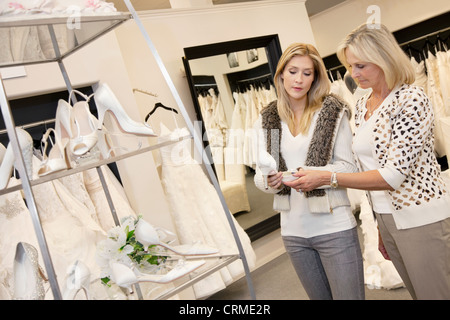 Young woman with senior mother looking at footwear in bridal store - Stock Photo