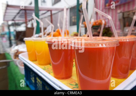 Close-up of fruit juices on display at market stall - Stock Photo