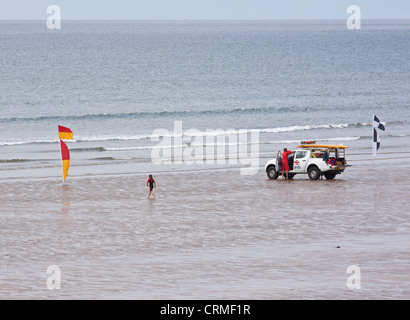 A child heads towards the sea near a lifeguard patrol on the beach at Westward Ho, England between flags indicating - Stock Photo