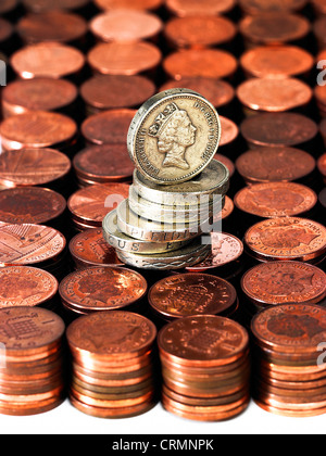 Neat piles of British pennies with a pile of one pound coins - Stock Photo