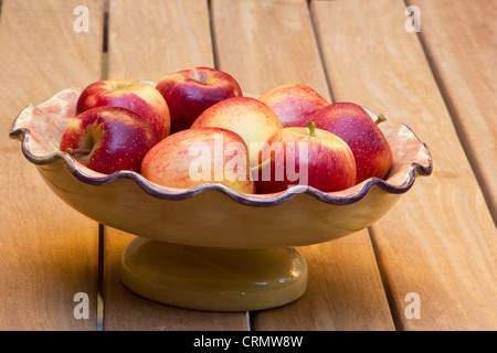 Red apples in a fruit bowl on wooden table - Stock Photo