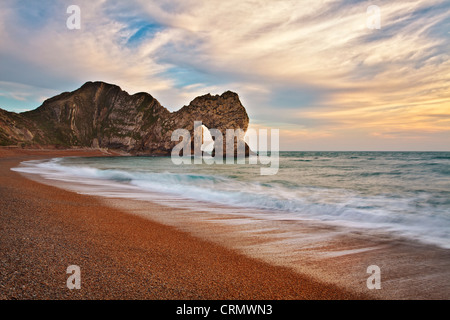 The rock arch of Durdle Door at sunset. - Stock Photo
