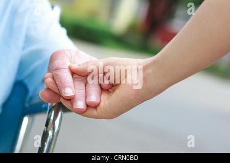 Senior women in wheelchair holding hands with caretaker - Stock Photo