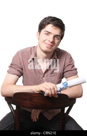 High school male graduate holding his graduating diploma sitting on a chair on a white background - Stock Photo