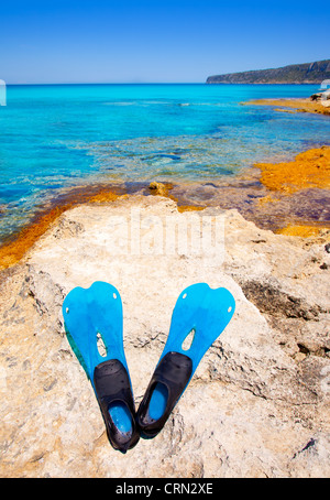 Balearic Formentera island with scuba diving blue fins on a rock - Stock Photo