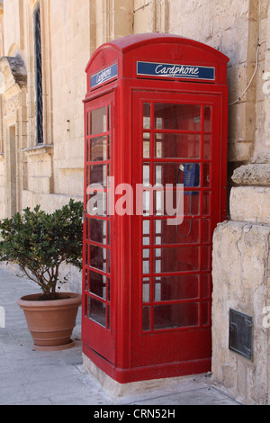 Traditional English red phone booth standing by the wall in Malta - Stock Photo
