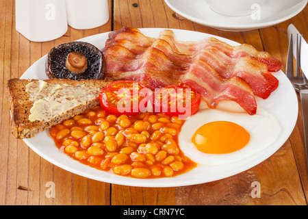 Full English breakfast on an old pine kitchen table. - Stock Photo