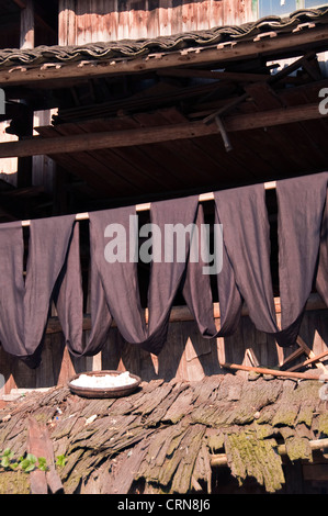 Indigo dyed fabric hanging to dry in the sun - Dong village of Zhaoxing, Guizhou province - China - Stock Photo