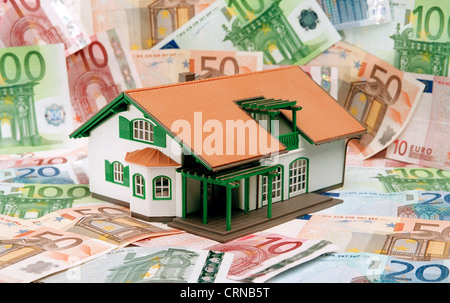 A model house stands on bills - Stock Photo