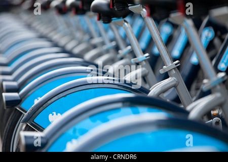 A row of Barclays Cycle hire scheme bikes in a docking station. - Stock Photo