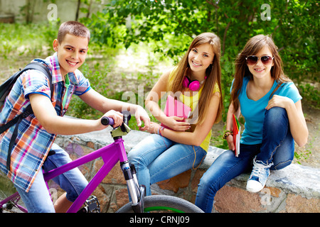 Guy on the bike stopping beside two beautiful girls - Stock Photo