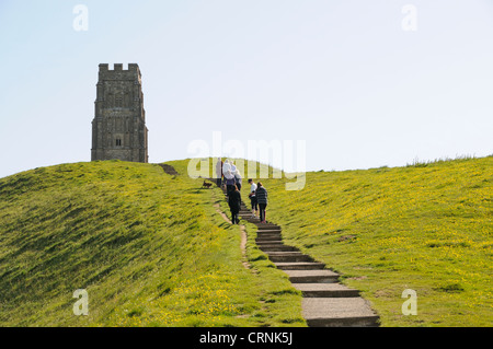 Tourists climbing the path to Glastonbury Tor to St. Michael's Tower. - Stock Photo