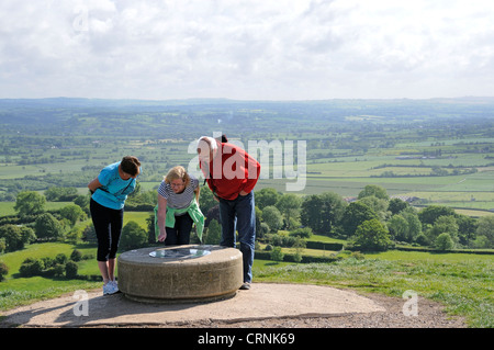 Tourists looking at the viewfinder map on the summit of Glastonbury Tor. - Stock Photo