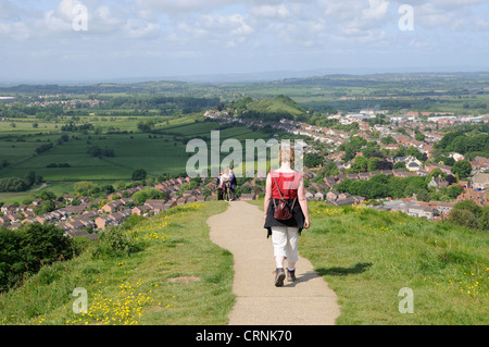 Walkers on a path leading down from Glastonbury Tor towards the town. - Stock Photo