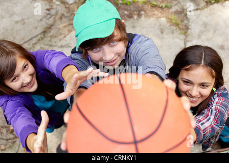 Cheerful teens playing basketball in the street holding the ball close to the camera - Stock Photo
