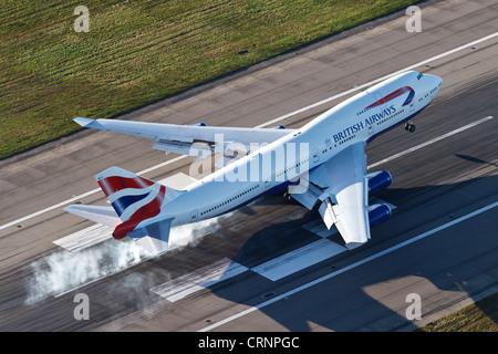 Aerial view of a British Airways Boeing 747 landing on Runway 27R at London Heathrow Airport. - Stock Photo