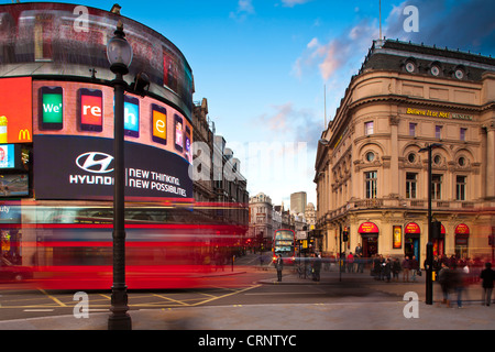 Red London double decker bus travelling through Piccadilly Circus in London's West End. - Stock Photo