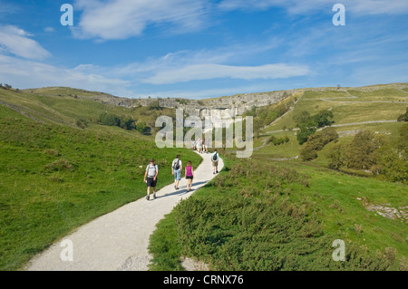 People walking along a footpath leading to Malham Cove, a spectacular curved limestone formation in the Yorkshire - Stock Photo