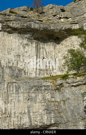 People rock climbing on Malham Cove, a spectacular limestone crag formed after the last ice age. - Stock Photo