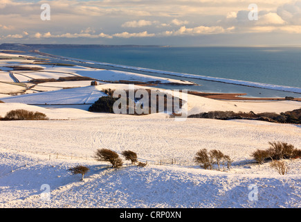 View of snow-covered hills around Abbotsbury, with St Catherine's Chapel, the Fleet and Chesil Bank in the background. - Stock Photo