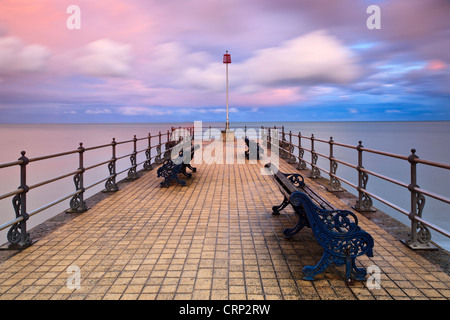 View over benches on the Banjo shaped Jetty in Swanage Bay. - Stock Photo