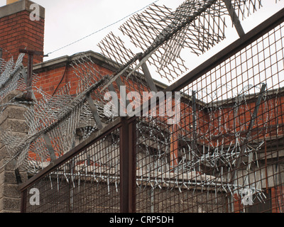 Security measures fence, barbed  razor wire, spikes on the outside of a red brick building in Ireland - Stock Photo