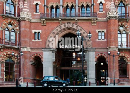 A black taxi cab waiting outside St Pancras Renaissance Hotel. - Stock Photo
