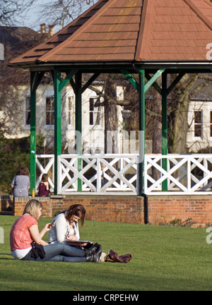Two young women relaxing on the grass in front of the bandstand in  Parson's Close Recreation Ground. - Stock Photo