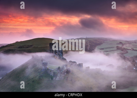The ruins of Corfe Castle rising through the morning mist. - Stock Photo