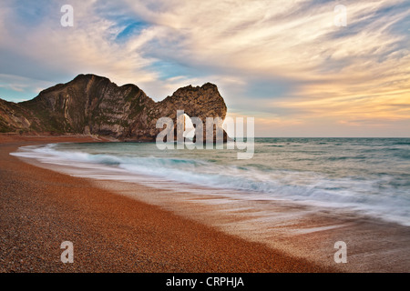 Durdle Door, a natural Limestone arch near Lulworth Cove, part of the UNESCO Jurassic Coast at sunset. - Stock Photo
