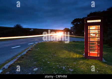 Light trail from a car passing a red telephone box by the side of a road in Dartmoor National Park. - Stock Photo