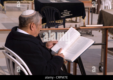 Jewish man reads from the Torah at the Old City's Western Wall, Jerusalem, Israel - Stock Photo