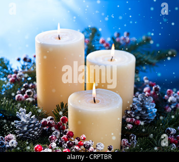 Three candles in an advent flower arrangement for advent and Christmas with snow fall - Stock Photo